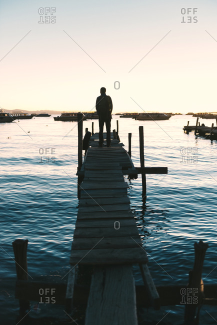 Man standing on wooden boardwalk looking the Titicaca Lake at sunset, Bolivia