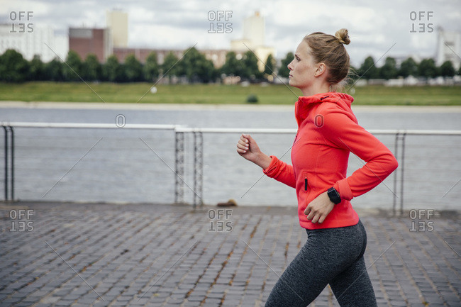 Young woman jogging at River Rhine