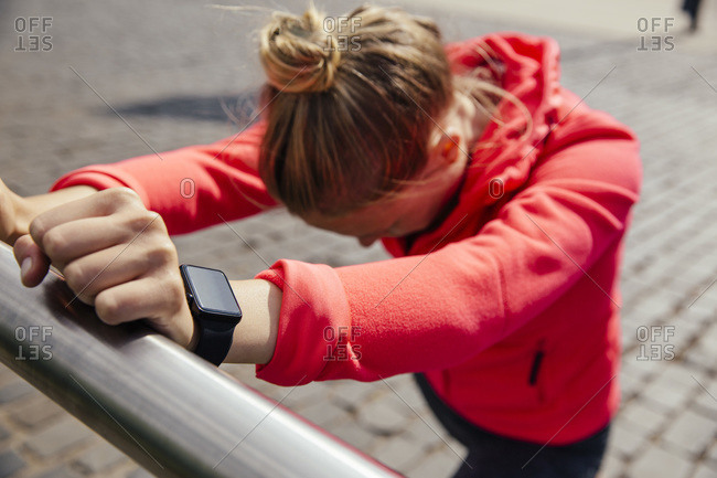 Young sporty woman with smart watch stretching