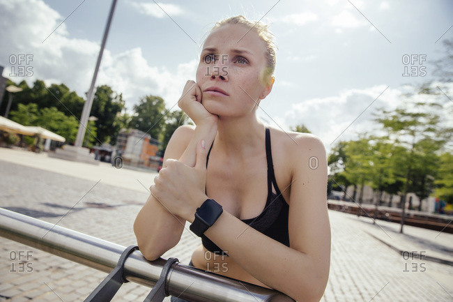 Young sporty woman with smart watch leaning on railing
