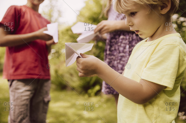 Three children playing with paper planes in garden
