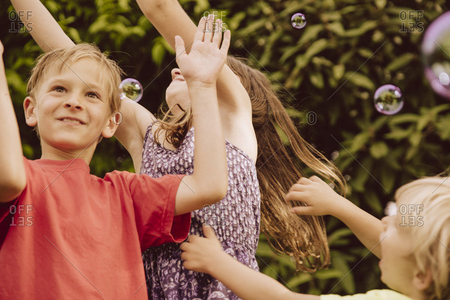 Three children playing with blow soap bubbles in garden
