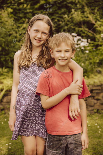Smiling girl putting arm around her brother in garden