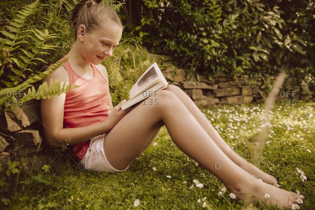 Girl reading a book in garden