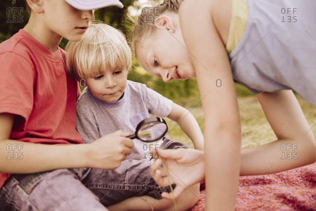 Three children on blanket looking through a magnifying glass