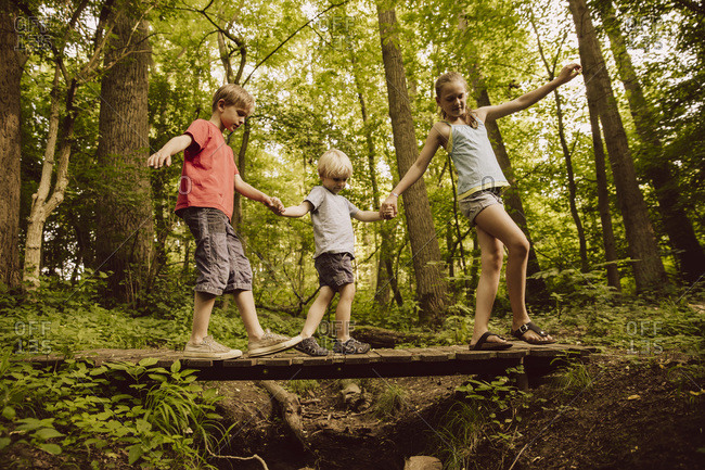 Three children balancing along a small bridge in forest