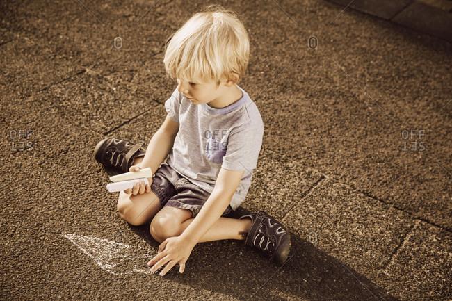 Boy using sidewalk chalk on tarmac