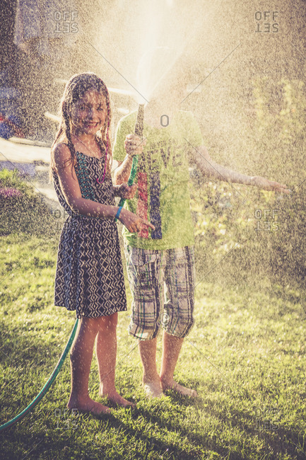 Two children splashing with water in the garden