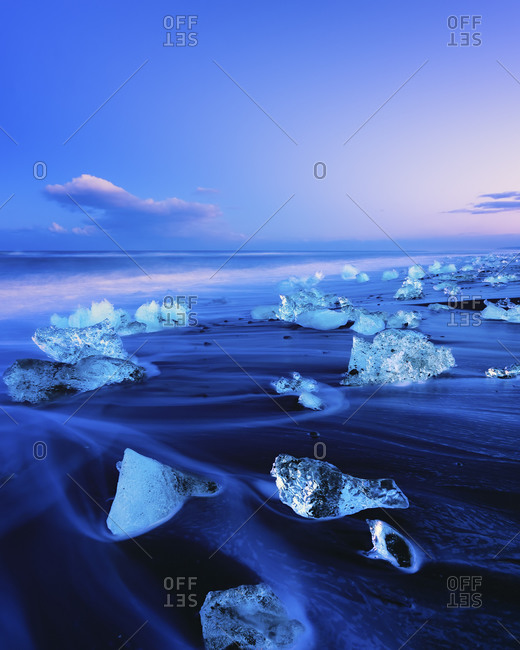 View to glacial lake Jokulsarlon, glacier ice on beach at twilight