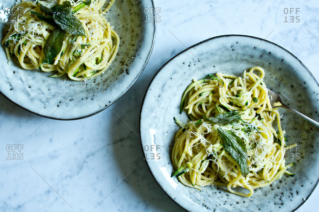 Two dishes of garlic and zucchini pasta