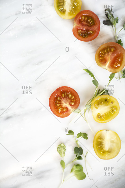 Tomatoes and microgreens arranged on a marble surface