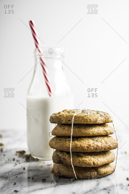Bottle of milk and stack of cookies on white marble surface