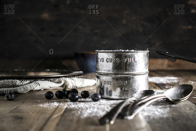 Blueberries on a rustic table with measuring cup and spoons
