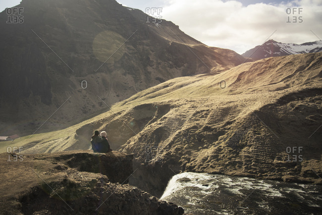 A couple admires a waterfall in the mountains