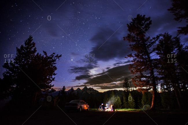 Friends gathered around a campfire under the night sky