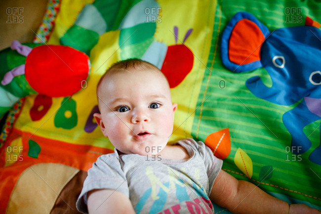 Bright-eyed infant lying on a play mat