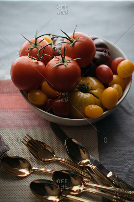 Various tomato varieties in a bowl by silverware