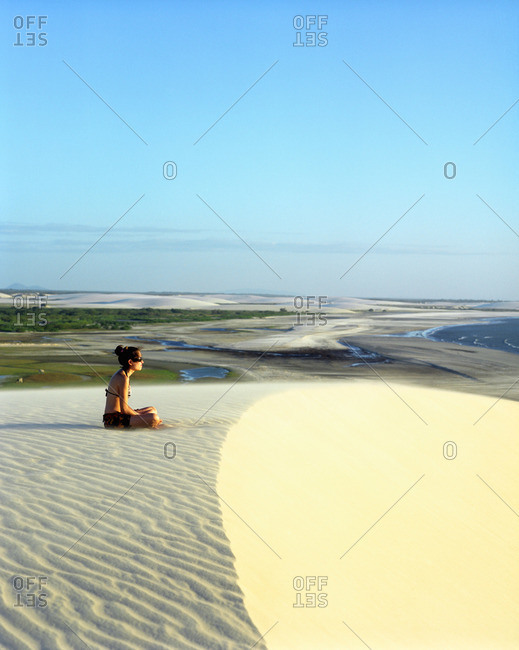 Jericoacoara, Brazil - June 20, 2007: Young woman meditates at Sunset Dune, Brazil