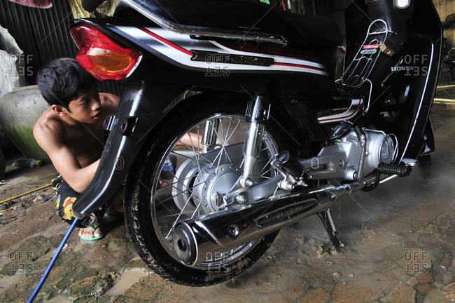 Kratie, Cambodia - September 26, 2012: A mechanic repairing a motorbike, Kratie, Cambodia