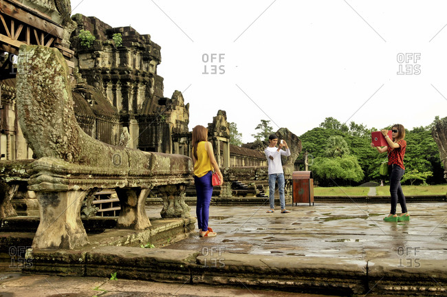 Angkor, Cambodia - September 15, 2012: Tourists take pictures in Angkor, Cambodia