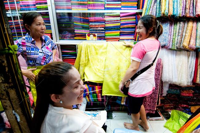 Phnom Penh, Cambodia - October 1, 2012: Three women shopping for fabric in the market, Phnom Penh, Cambodia