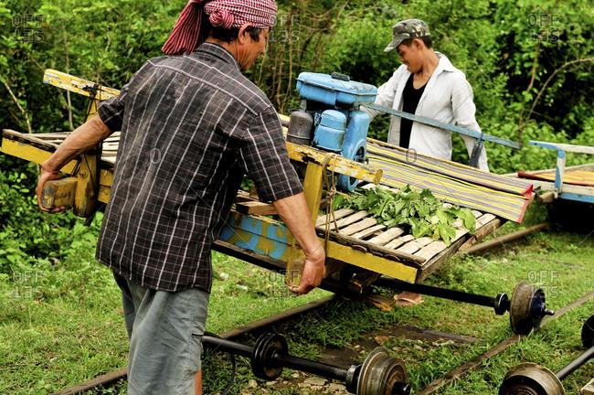 Battambang, Cambodia - September 19, 2012: Two men moving a bamboo train off a track in Battambang, Cambodia