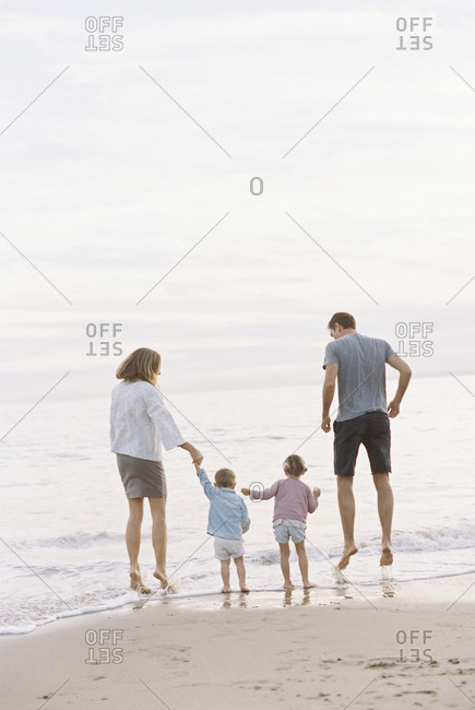 Couple playing with their son and daughter on a sandy beach by the ocean, holding hands