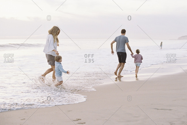 Couple playing with their son and daughter on a sandy beach by the ocean