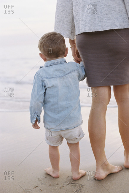 Woman standing on a sandy beach by the ocean, holding her young son's hand
