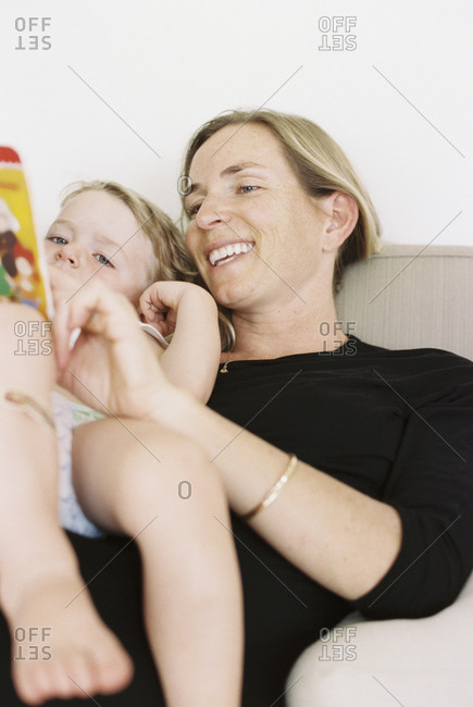 Woman sitting on a sofa, holding a book, reading to her daughter