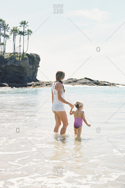 Woman playing with her daughter on the beach