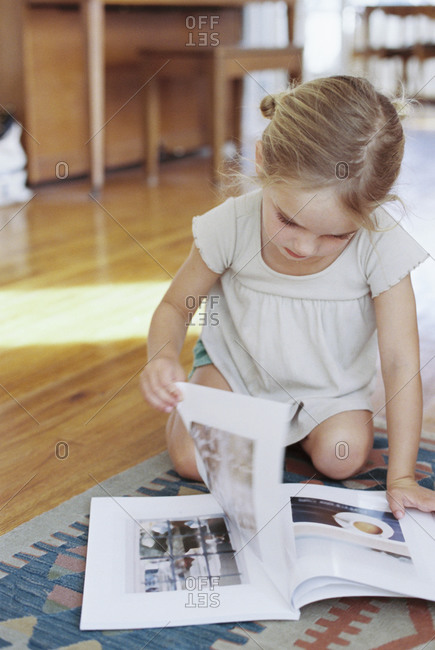 Young girl sitting on the floor, reading a lifestyle magazine