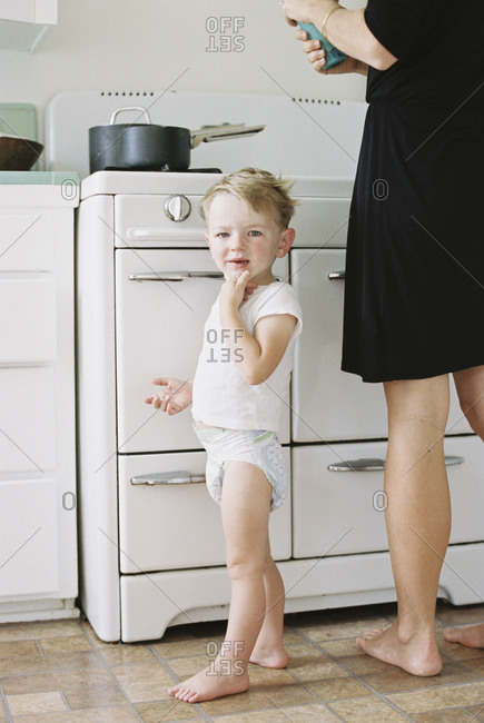 A woman and a child, a young boy standing barefoot in a kitchen