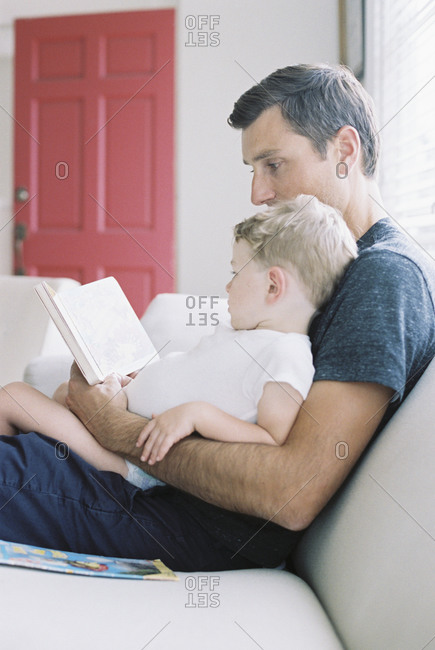 Man sitting on a sofa with his son sitting on his lap, holding a book, reading a story