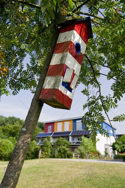 Striped birdhouse in a tree