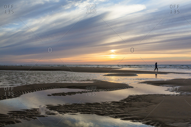 Woman walking through tidal pools on a beach at sunset
