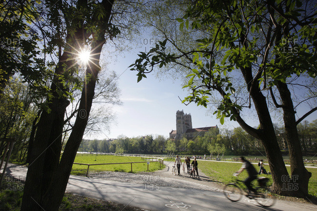 Munich, Germany - April 26, 2012: People biking in a park along the Isar River in Munich, Germany