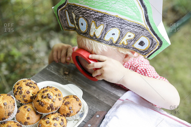 Little boy with a paper hat looking at muffins