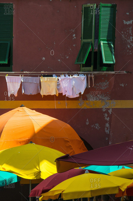 Clothes hanging on a line above outdoor umbrellas