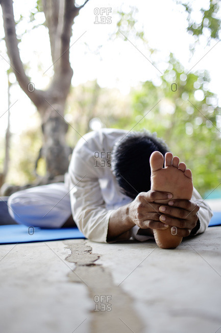 Young man stretching into a yoga pose