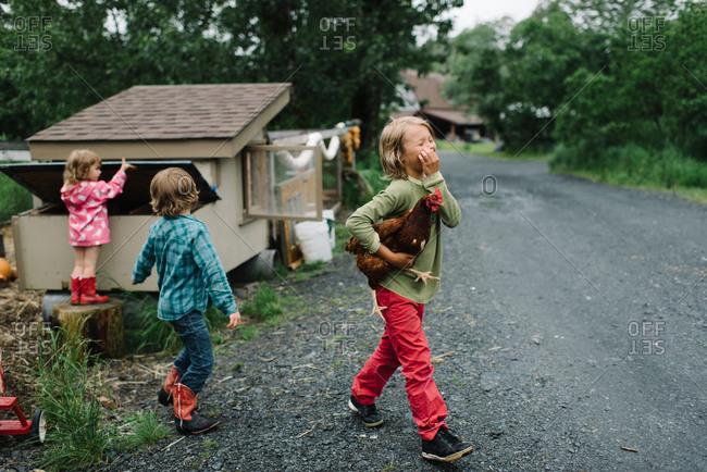 A boy walks away from a chicken coop holding a chicken