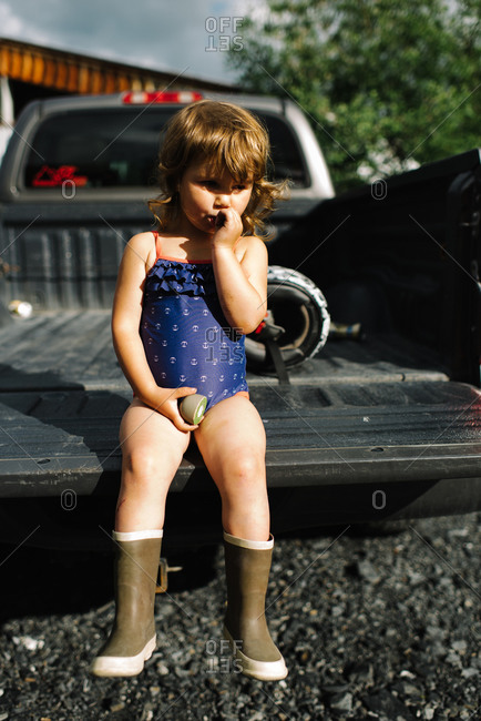 A girl sits in the back of a pickup truck