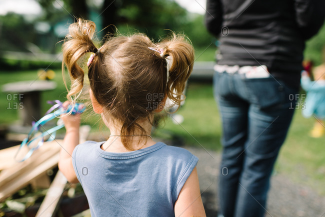 A little girl with pigtails in a park