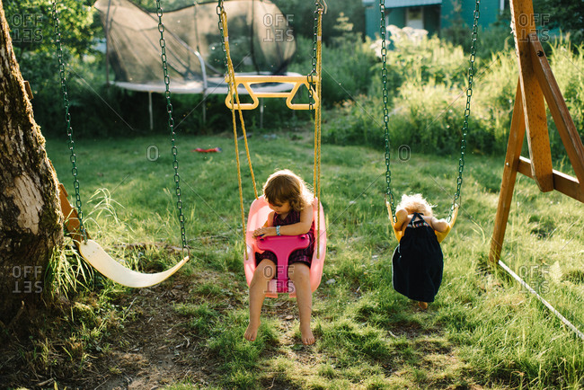 Two little girls swing on a swing set