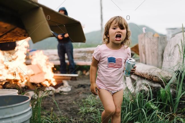 A girl yells at a bonfire