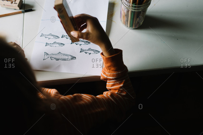 A boy makes a fish picture with stamps
