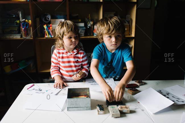 A brother and sister make pictures with stamps