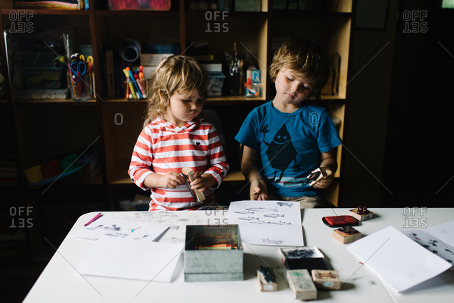 A brother and sister look at the pictures they've made with stamps