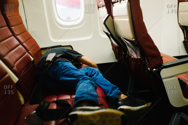 A boy sleeps on an airplane
