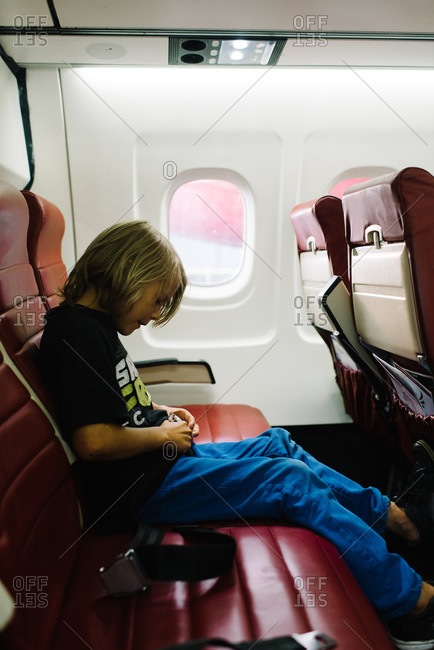 A boy buckles his seatbelt on an airplane